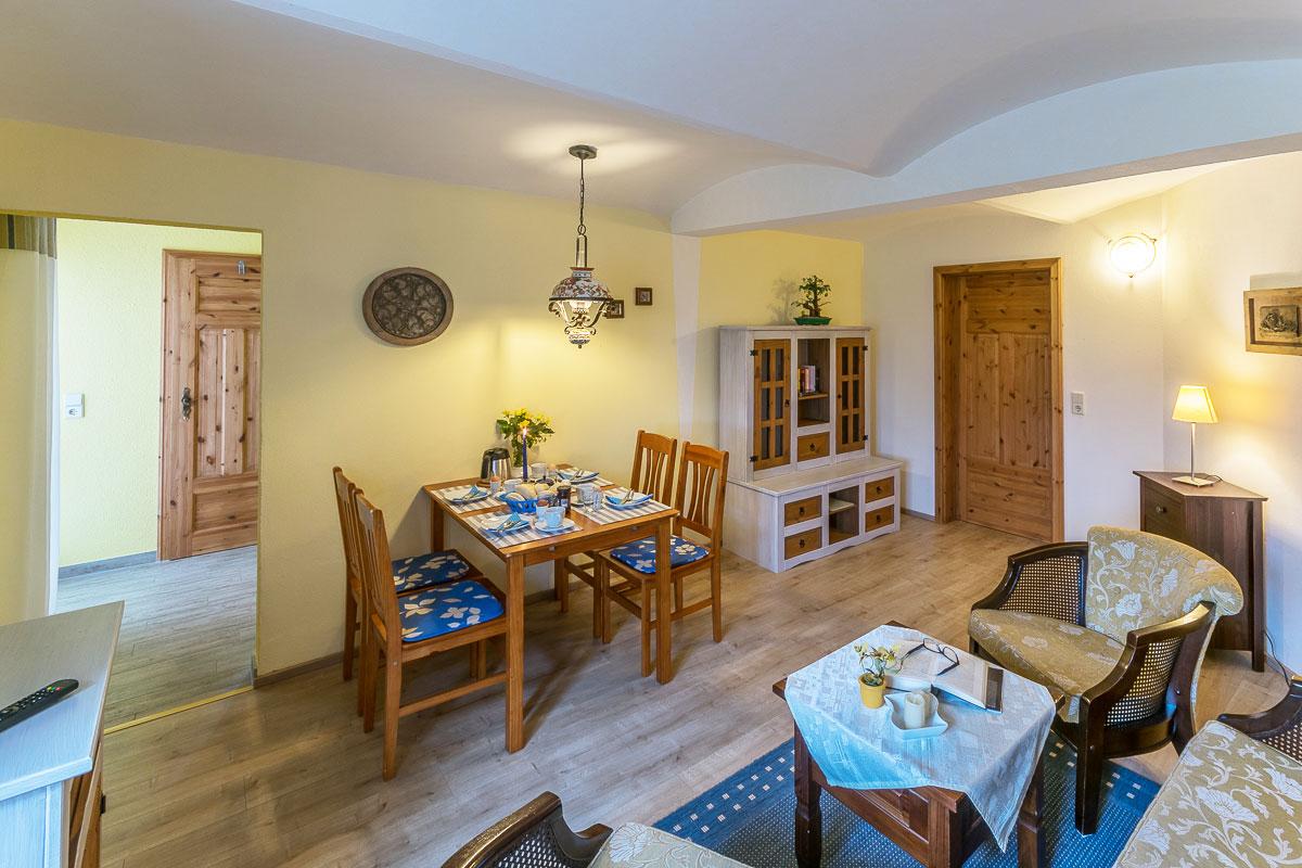 Ferienwohnung Papststein - Wohnzimmer mit Sitzecke und Esstisch